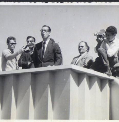 O então governador Paulo Pimentel discursando na Praça Willy Barth, por ocasião de sua visita a Marechal Cândido Rondon. Da esquerda a direita: 1º a 3º - não identificados; 4º - Paulo Pimentel; 5º e 6º - não identificados; 7º - pastor Harald Malschitzky; e 8º Pastor Joachim Pawelke. Imagem: Acervo Memória Rondonense - FOTO 1 -