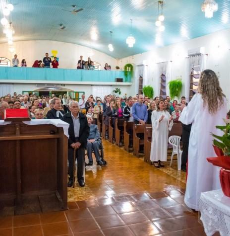 Aspecto da celebração do cultivo comemorativo aos 60 anos da Comunidade Evangélica de Iguporã. Da esquerda a direta: atrás do senhor de camisa listrada, o pioneiro Frederico Ribeiro; em seguida ... Model (de camisa branca com listras azuis, na horizontal; a frente, Alceu Storck; a sua frente, seu pai Arnaldo Storck (meio rosto e camisa vermelha); atrás, Sofia (Grohmann) Model (de óculos e tiara no cabelo); ao seu lado, o marido Arlindo Model ( de camisa bege); bem a frente, de óculos, Gertrudes (Lange) Koch; Pastor sinodal Lauri Becker; a sua frente, Edmundo Koch (de blusa escura); e na cadeira de rodas, Adolfo Herpich.  À direita do corredor: pastor Flávio Antonio Hepp (de camisa azul) e esposa; à frente, pastora estagiária Fabiane Schmidt (de túnica branca); e a pastora Nádia Becker ( de costas).  Imagem: Acervo Paróquia Evangélica Esperança em Cristo/Facebook - FOTO 14 -