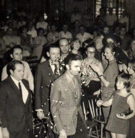 Almiro Bauermann recepcionado na entrada do salão do Clube Aliança, seguido pelos vereadores Salvino Wanderlinde (de paletó escuro), Noori Pooter (de camisa branca) e Ilvo Grellmann, a direita, (de paletó escuro).  Imagem: Acervo Almiro Bauermann - FOTO 2 -