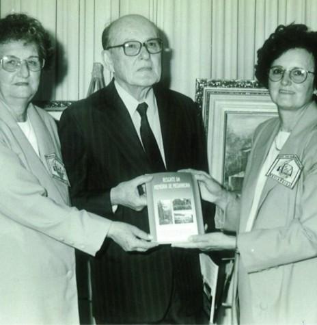 O pioneiro Pedro Soccol recebendo  das professora Elza Lorenzoni Biesdorf e Hilegarde Maria Rohde, um exemplar do livro