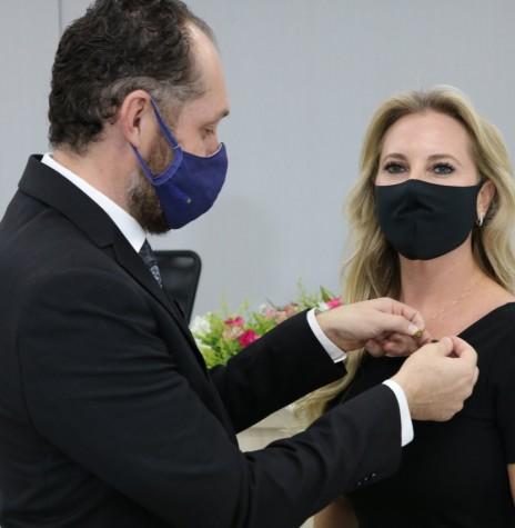 Empresária Carla Rieger Bregoli recebendo o pin de presidente da Acimacar de seu antecessor arquiteto e urbanista Ricardo Leites de Oliveira.  Imagem: Acervo Acimacar - FOTO 19 -