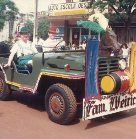 Pioneiro Benno Weirich (de chapéu verde), num desfile  de Oktoberfes, na Rua Sete de Setembro, tendo ao seu lado o filho Ilo e atrás do jipe numa charrete seus familiares.  Imagem: Acervo Andrea Weirich - FOTO 4 -