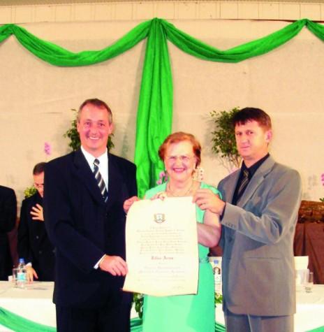 Zilda Arns Neumann recebendo o título de cidadão honorária de Marechal Cândido Rondon, tendo a sua direita o prefeito municipal Edson Wasem e a esquerda o vereador Nilson Hachmann.  Imagem: Acervo Memória Rondonense - FOTO 1 -
