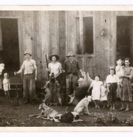 Em frente ao barracão da Maripá, entre out.-nov./1950, onde moravam estas famílias. Da esquerda para a direita: WEIRICH, Alice com os gêmeos Cláucio (faleceu de crupe em dez./1950) e Cláucia, o menino Ilo e o pai Benno (os dois segurando espingardas), Lauro (segurando uma espingarda e uma pele de onça); GRIEBELER, Arlindo, as filhas Silda, Realda (tocando os borrachudos) e Brunilda, a esposa Hilda com a filha Luíza no colo; SCHEFLLER, Ida com um filho no colo (o marido e o outro filho haviam saído). Elaborado por Lia Dorotéa Pfluck, em 2000. FOTO Acervo de Alice Weirich, cedida em 1995. PFLUCK, 2013, p. 109. Imagem: Acervo Dr.a Dorotéa Pfluck