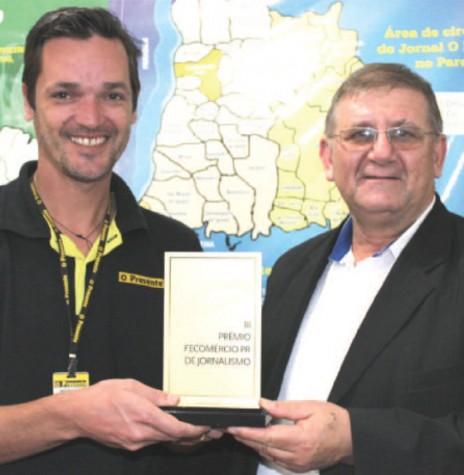 Jornalista Giuliano de de Luca recebendo  o prêmio Fecomércio de Jornalismo 2015 das mãos de Ademar Bayer, presidente do Sindicato do Comércio Varejista de Marechal Cândido Rondon.  Imagem: Acervo O Presente - FOTO 12  -