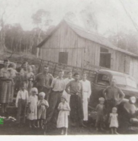 Chegada da família Graff a sua primeira morada na então Linha 4 Irmãos, hoje Linha Concórdia, fotografada logo após descarregar a mudança, junto com os parentes que já moravam nas proximidades e o motorista do caminhão. De branco dois paraguaios que faziam as primeiras roçadas dos colonos (Informação e Imagem: Vilton Graff) - FOTO 1 -