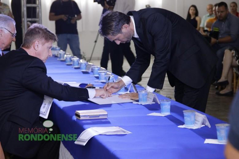 Professor Márcio Andrei Rauber assinando o termo de posse em sessão solene da Câmara Municipal de Marechal Cândido Rondon, realizada no Clube Aliança.  Imagem: Acervo Memória Rondonense.