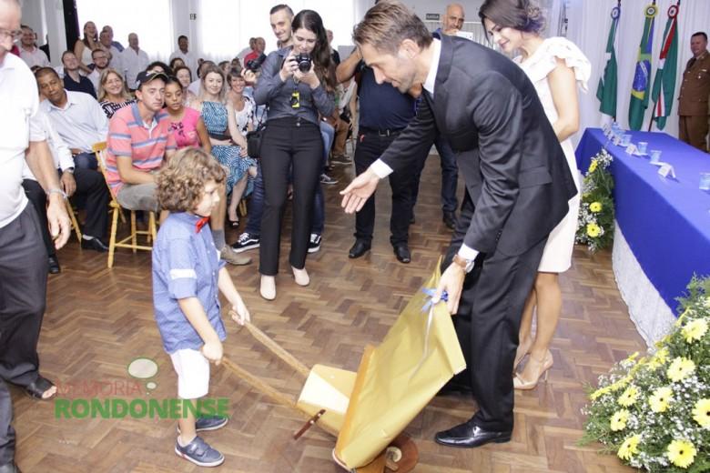 Prefeito empossado Márcio Rauber recebendo a peça de arte do filho João Pedro.  Imagem: Acervo Memória Rondonense - Crédito: Tioni de Oliveira