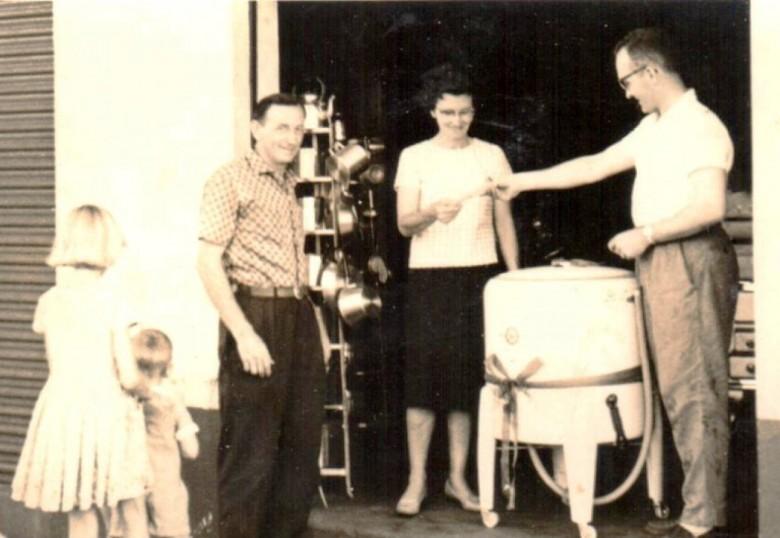 Senhora Norma Lamb recebendo de Norbert Rieger, representante da Casa Rieger referente a aquisição de uma máquina de lavar-roupas.  À esquerda, Arlindo Alberto Lamb, marido da senhora Norma.