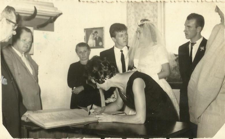 Outro instante da celebração do casamento no Civil, de Arno Ervino Ritter e Nercy Koch.  Da esquerda a direita:   1ª -cartorário Willy Carlos Trentini; 2ª - empresário Hedo Schneider, padrinho de casamento do noivo; 3ª - Erna  Ritter; 4ª - noivo Arno Ritter; 5ª - noiva Nercy Koch;  6ª - Plínio Ritter, irmão do noivo; 7ª - Helmuth Koch;  e 8ª - Aida Schneider, madrinha de casamento assinando o  livro de assentamento.