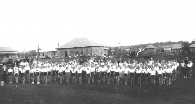 Alunos do Grupo Escolar General Rondon, em solenidade na atual Praça Dealmo Selmiro Poersch.  Ao fundo, o antigo Salão Wayhs, em  1960.