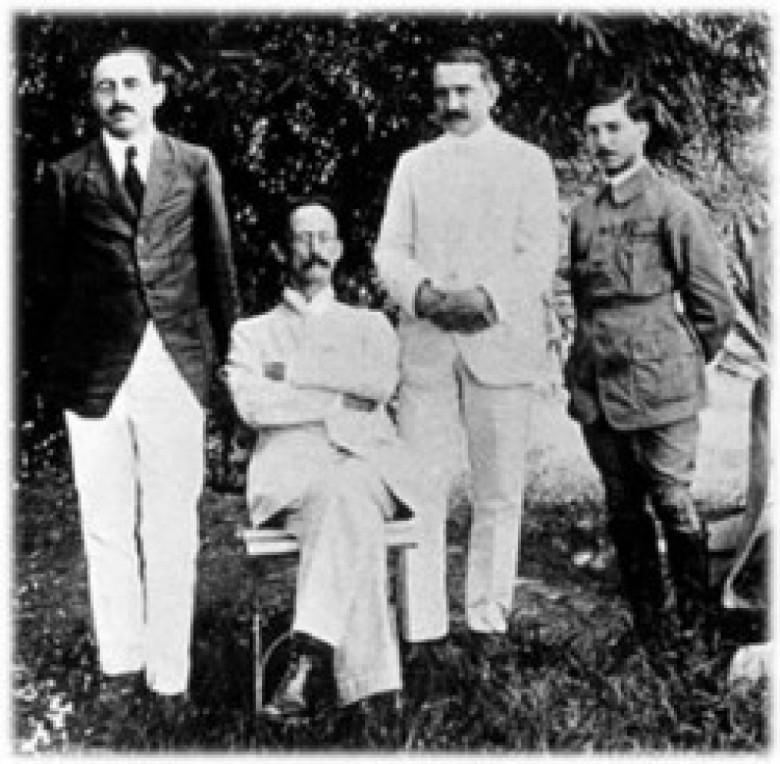 Sentado, Adolfo Lutz tem, à sua esquerda, Heráclides-César de Souza Araújo e Olympio da Fonseca, á sua direita, Luiz E. Migone. Fotografia tirada em San Bernardino, Paraguai, em 1918.  Imagem: Acervo Instituto Adolfo Lutz -  São Paulo - Capital
