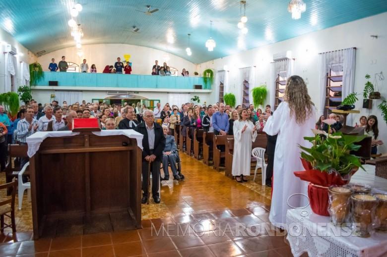 Aspecto da celebração do cultivo comemorativo aos 60 anos da Comunidade Evangélica de Iguporã. Da esquerda a direta: atrás do senhor de camisa listrada, o pioneiro Frederico Ribeiro; em seguida ... Model (de camisa branca com listras azuis, na horizontal; a frente, Alceu Storck; a sua frente, seu pai Arnaldo Storck (meio rosto e camisa vermelha); atrás, Sofia (Grohmann) Model (de óculos e tiara no cabelo); ao seu lado, o marido Arlindo Model ( de camisa bege); bem a frente, de óculos, Gertrudes (Lange) Koch; Pastor sinodal Lauri Becker; a sua frente, Edmundo Koch (de blusa escura); e na cadeira de rodas, Adolfo Herpich.  À direita do corredor: pastor Flávio Antonio Hepp (de camisa azul) e esposa; à frente, pastora estagiária Fabiane Schmidt (de túnica branca); e a pastora Nádia Becker ( de costas).  Imagem: Acervo Paróquia Evangélica Esperança em Cristo/Facebook - FOTO 7 -