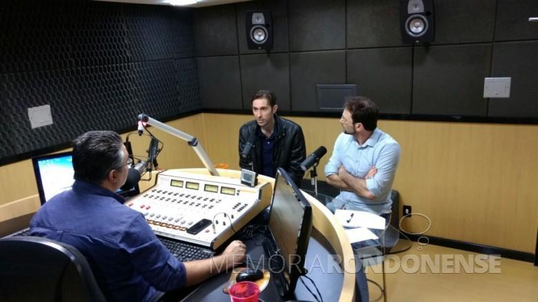 Márcio Rauber entrevistado no estúdio da Difusora FM pelos comunicadores Adriel Marcelo (camisa azul, de costas) e César Rech, à direita de braços cruzados.  Imagem: e crédito: Tioni de Oliveira - FOTO  7 -