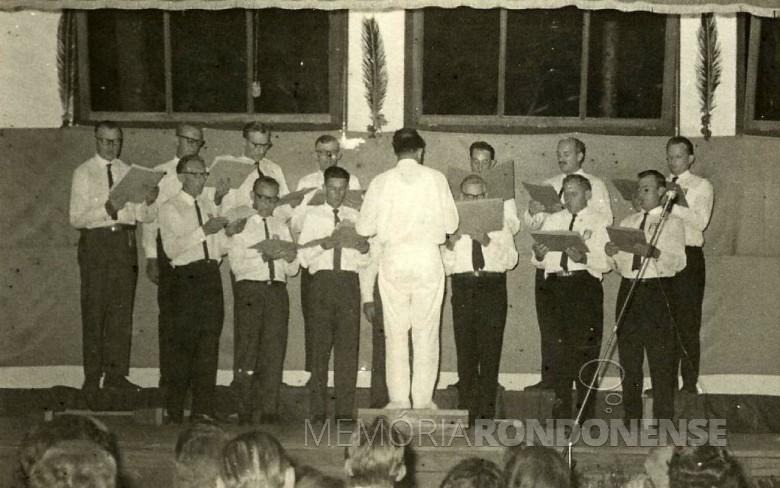 Coral masculino do Clube Aliança se apresentado na cidade de Hohenau, Paraguai, em 10 de fevereiro de 1971.  Da esquerda à direita, ao fundo: Bertoldo Guthoff, 2º, 3º 4 º - não identificados, Oswaldo Heinrich, Simão Scherer, 7º - não identificado.  Á frente: Arlindo Schwantes, Heinz Baumann, Tito Debus, dirigente Sigismundo Heinrich (de costas),  5º - não identificado, Edvino von Borstel e Almo Schroeder.  Imagem:  Acervo Tito Debus - FOTO 4 -