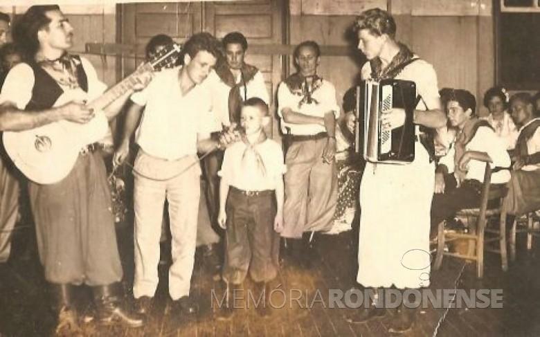 Walter Basso (menino de 6 a 7 anos), se apresentando no baile  estilo gaúcho, no então Salão Wayhs.  Da esquerda à direita: 1ª - de violão, não identificado; 2ª - Ari Reis (Xuxú), de microfone; 3ª - Walter Basso; 4ª - Egon Seefeld, de acordeão. Demais pessoas não identificadas.  Imagem: Acervo Walter Basso - FOTO 1 -