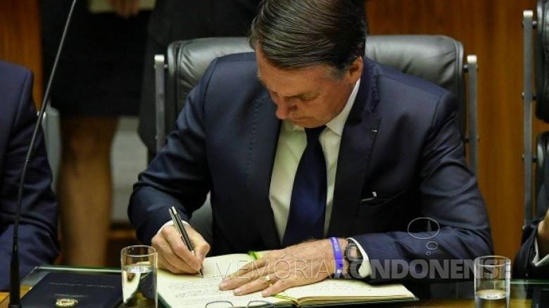 Jair Messias Bolsonoro assinando o termo de posse no Congresso Nacional.  Imagem: Acervo AFP - Crédito: Nelson Almeida - FOTO 38 -
