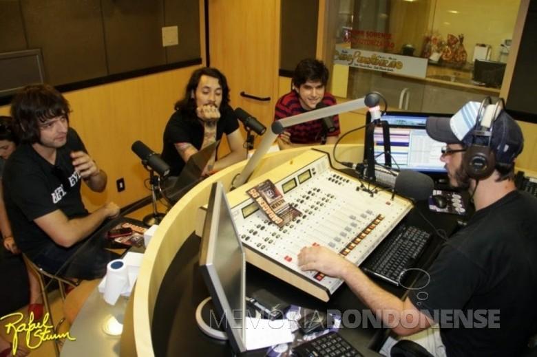 Jornalista Cristiano Viteck entrevistando Rodolfo Kruger (e), baixista da banda Cachorro Grande, e Chapola (m) e Nevilton Alencar, baterista e vocalista do Grupo Nevilton, em 2012, no programa Garagem 95.  Imagem: Acervo particular - FOTO 3 -
