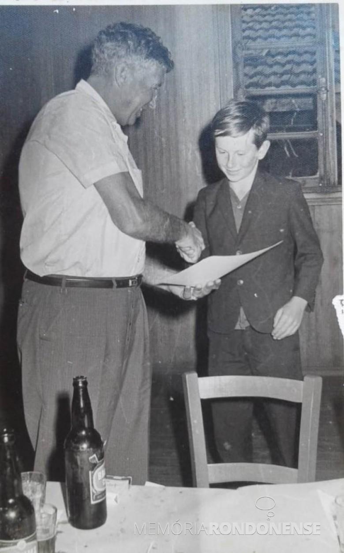 Jovem Moacir Froehlich recebendo das mãos do prefeito municipal Dealmo Selmiro Poersch, de Marechal Cândido Rondon, o certificado de conclusão do curso de operador de trator.  Imagem: Acervo pessoal - FOTO 3 -