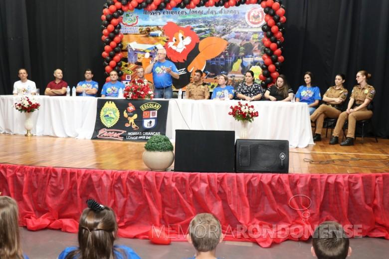 Prefeito Leomar Rohden (Mano), de Pato Bragado, discursando junto a mesa de honra da solenidade de formatura do Proerd de turma da Escola Municipal Marechal Deodoro.  Imagem: Acerco Imprensa - PM-Pato Bragado - Crédito: Marili Besso - FOTO 15 -