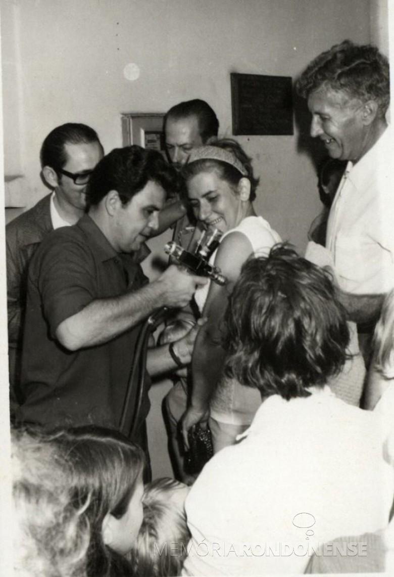 Primeira-dama Virica (nascida Zart) Poersch recebendo vacina contra varíola do secretário de Estado de Saúde,  Arnaldo Faivro Busato.  Na foto, ao fundo, da direita a esquerdade, vereador Nori Pooter e Renato Guzzoni - cirurgião-dentista. Á direita: prefeito municipal Dealmo Selmiro Poersch.  Imagem: Acervo Fundo Fotográfico de Marechal Cândido Rondon - FOTO 2 -
