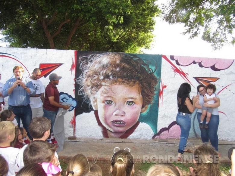 Solenidade de apresentação da grafitagem muro junto ao Colégio Luteranao Rui Barbosa.  À esquerda, o diretor Carlos Krache com dois grafiteiros e a aluna retratada.  Imagem: Acerco do Colégio - FOTO 9 -