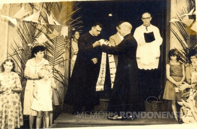 Padre Cristiano Weimann SVD recebendo a estola, simbolo da autoridade sacerdotal, de seu confrade João Assmann SVD, que lhe antecedeu como vigário da Paróquia Sagrado Coração de Jesus, da sede municipal de Marechal Rondon. Imagem: Acervo Memória Rondonense - FOTO 1 -