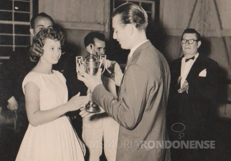 A jovem pioneira Lori Koch recebendo a taça do pioneiro Arno Roesler.  Não se descobriu o motivo da entrega do troféu.  Á direita, Willy Carlos Trentini, primeiro cartorário de Marechal Cândido Rondon .