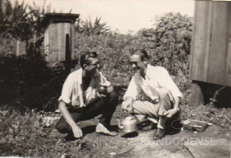 O pioneiro Alfredo Bausewein e um amigo nos anos de 1958/59.  Ao fundo, a famigerada casinha sanitária (capunga), para as necessidades fisiológicas.